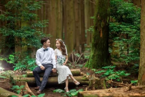 Couple poses for woodland photoshoot.