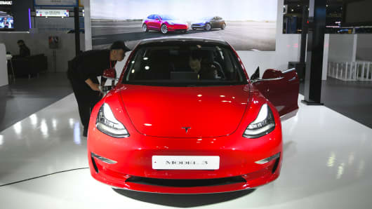 Visitors look at a Tesla Model 3 during a press preview of the Seoul Motor Show in Goyang, northwest of Seoul, on March 28, 2019.