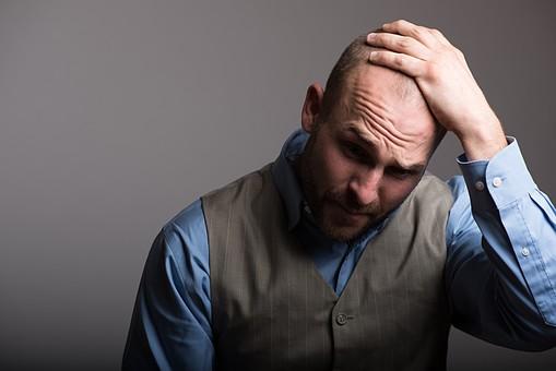 薄毛を気にして落ち込む外国人中年男性