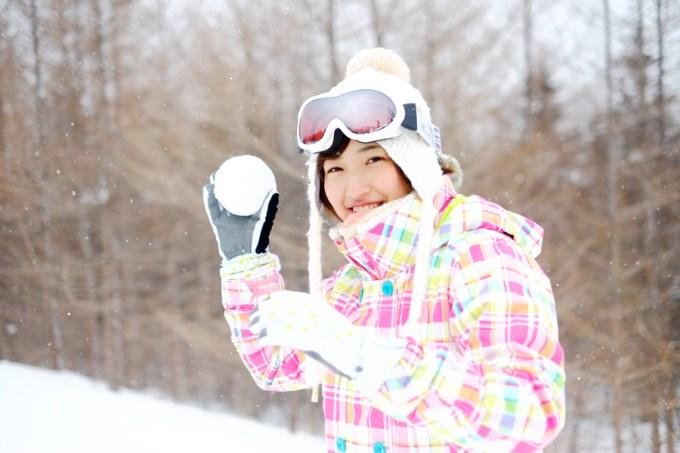 雪玉を持って微笑む若いアジア人女性