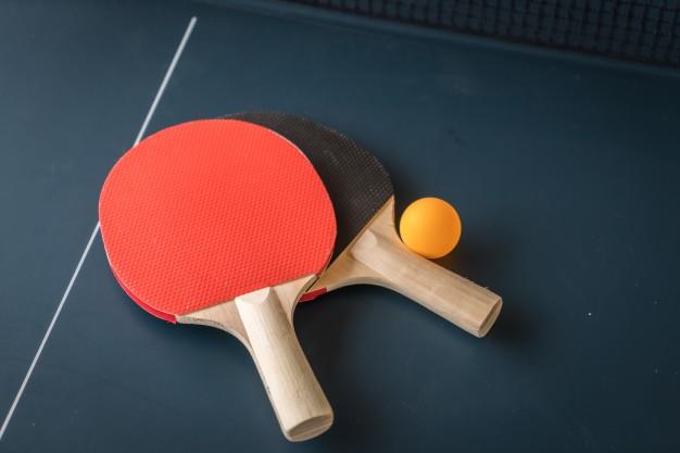 卓球台に置かれた赤と黒のラケットとオレンジの卓球ボール