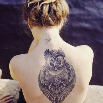 owl holding skull tattoo on upperback