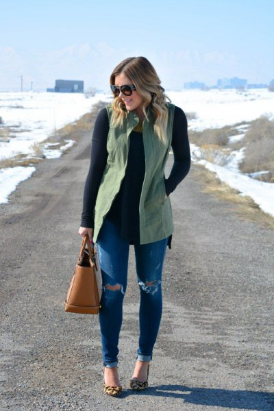 green vest over black skinny fit sweater