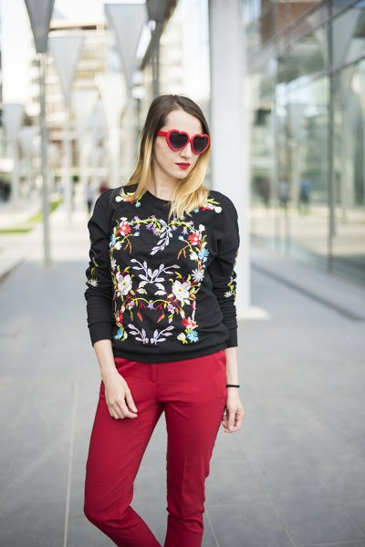 black embroidered sweatshirt with red jeans