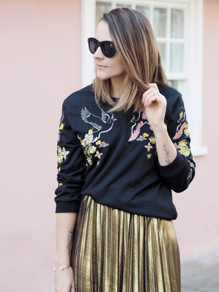 black sweater with gold pleated midi skirt