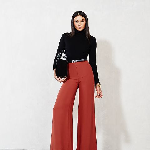 black turtleneck form fitting knit sweater with red wide leg pants