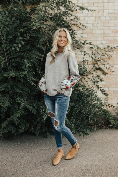 grey embroidered sweater with ripped skinny jeans