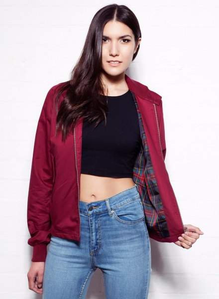 red harrington jacket with black crop top blue jeans