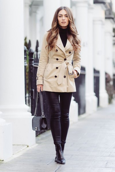 beige wrap coat with black turtleneck sweater and leather leggings