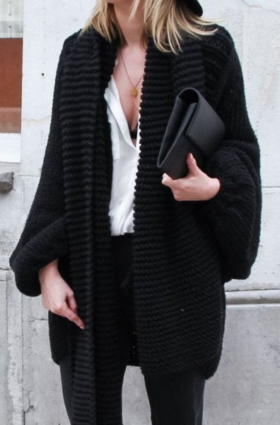 black chunky knit cardigan with white blouse and leather clutch bag