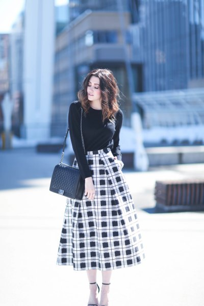 black crew neck sweater with high waisted midi flared checkered skirt
