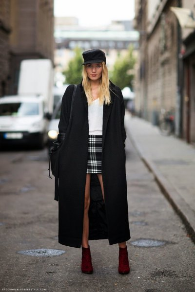 black maxi coat with white sweater and plaid mini skirt