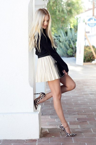 black mock neck knit sweater with white pleated mini skirt