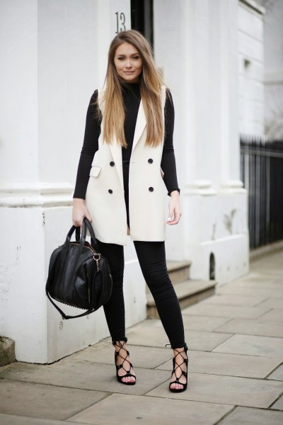 black turtleneck knit sweater with white sleeveless wool jacket