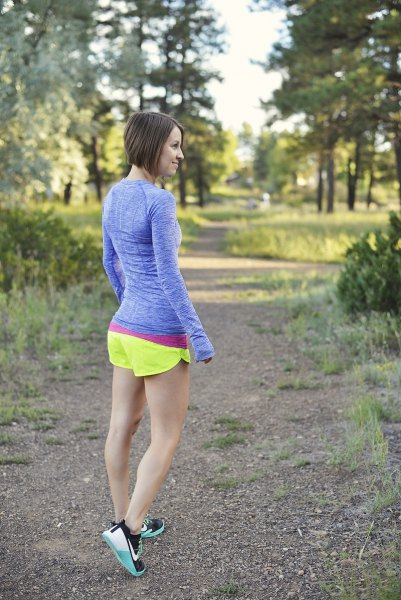 blue form fitting long sleeve tee with lemon yellow running shorts