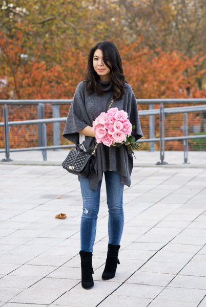 grey poncho sweater with blue skinny jeans and black boots