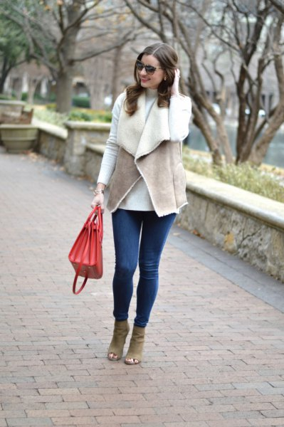 grey vest with white tee and blue skinny jeans