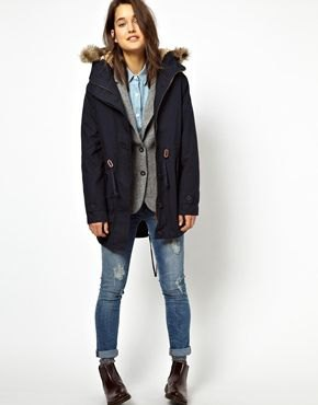 navy fur lined parka coat with grey vest and jeans