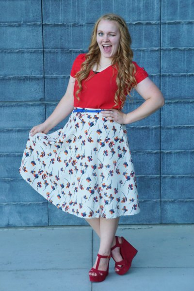 orange t shirt with white floral flared skirt and blue belt
