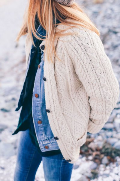 white cable knit cardigan over blue denim jacket