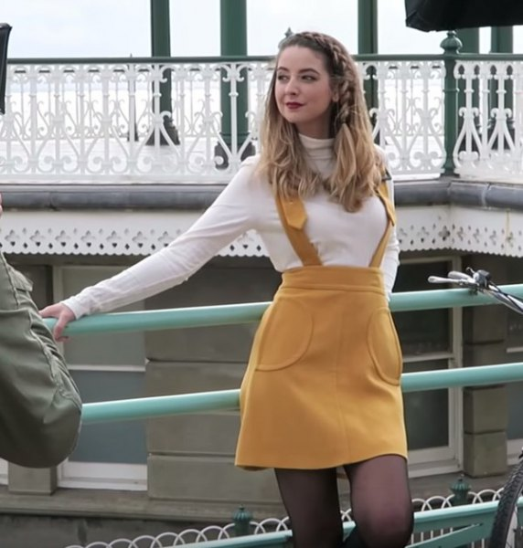 white mock neck fitted sweater with mustard yellow suspender mini dress