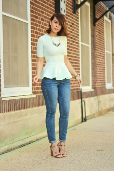 white peplum form fitting blouse with blue cuffed skinny jeans