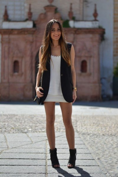 white scoop neck mini dress with black long sleeveless jacket