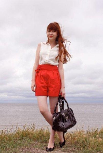 white sleeveless chiffon blouse with orange high rise pleated shorts