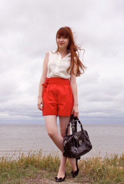 white sleeveless chiffon blouse with orange high rise pleated shorts