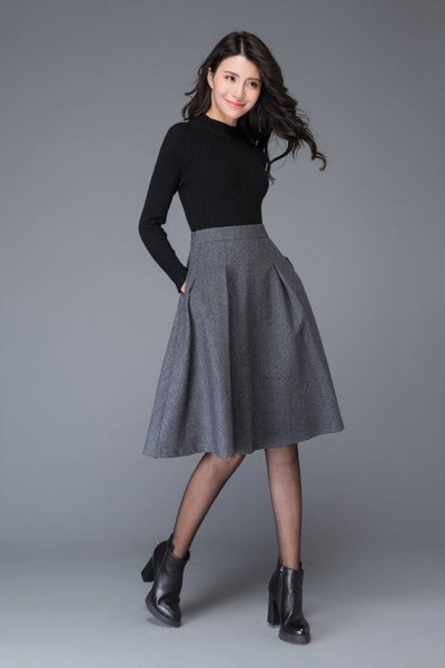 black form fitting long sleeve tee with midi grey flared wool skirt