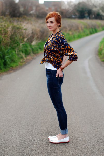 black printed shirt with dark blue skinny jeans and white loafers