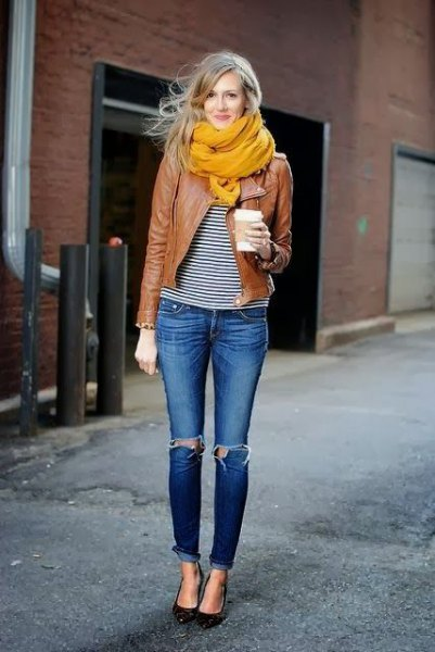 brown leather jacket with black and white striped tee and orange scarf