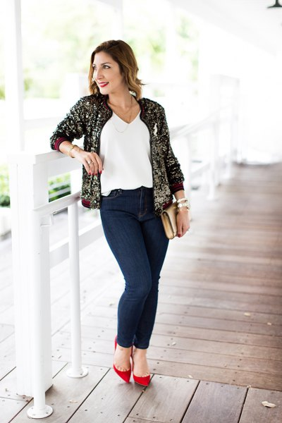 gold and black sequin bomber jacket with white v neck top and jeans
