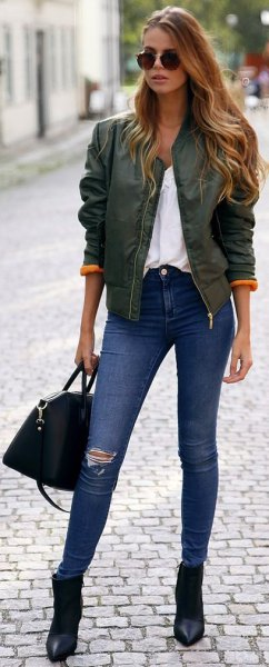 grey satin bomber jacket with white blouse and blue skinny jeans