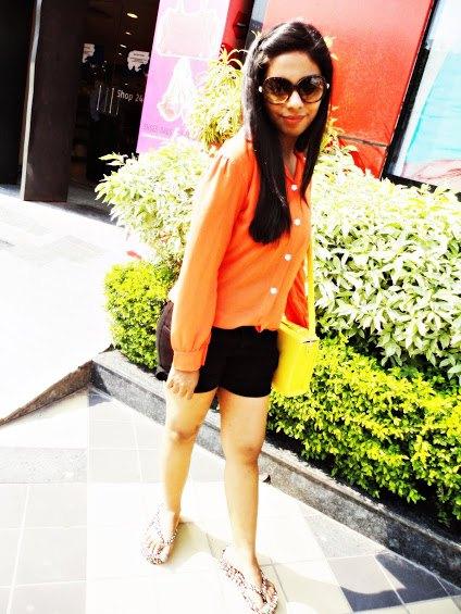 orange button up shirt with black mini shorts