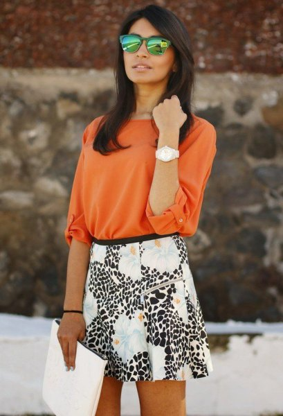 orange buttonless shirt with white and black printed mini skirt