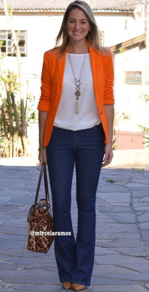 orange half sleeve blazer with white top and dark blue flared jeans