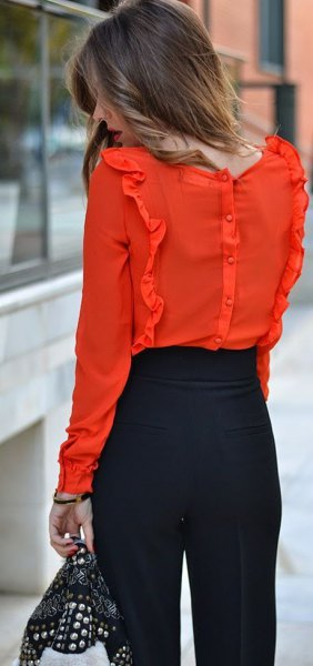 orange ruffle blouse with black chinos