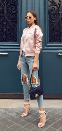 pale pink satin bomber jacket with heavily ripped cropped jeans
