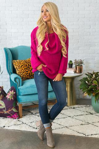 pink ribbed chunky sweater with cuffed jeans and grey boots