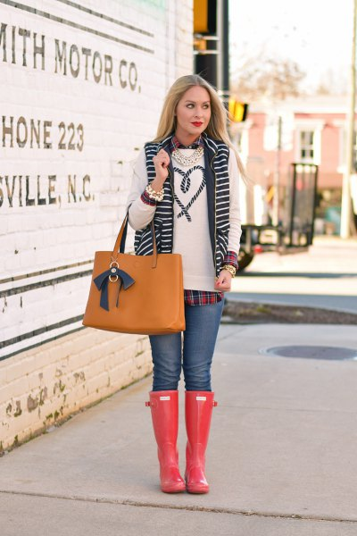 white embroidered sweater with blue jeans and orange knee high rain boots