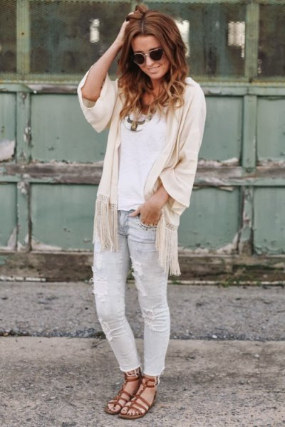 white top with ivory fringe half sleeve cape and light grey jeans