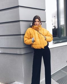 yellow puffer jacket with black wide leg jeans