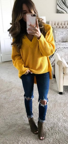 yellow v neck chunky knit sweater with blue skinny ripped jeans