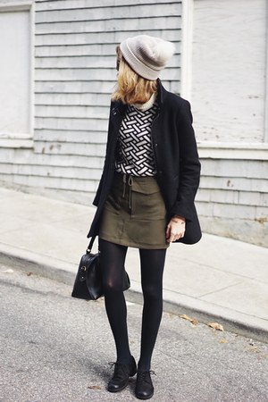 black and white patterned sweater with green mini tie waist skirt