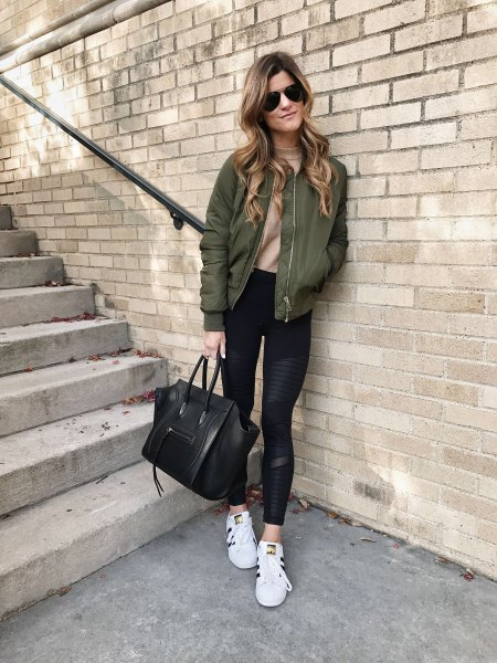 green bomber jacket with blush pink fitted sweater and running tights