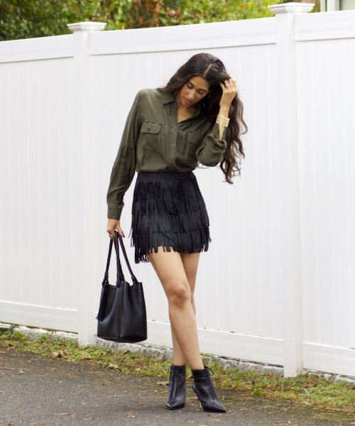 green front pocket button up shirt with black mini fringe skirt and boots