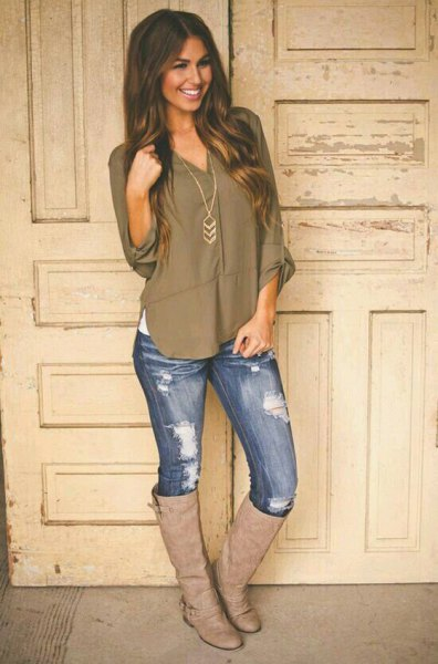 green v neck relaxed fit top with skinny jeans and brown leather boots