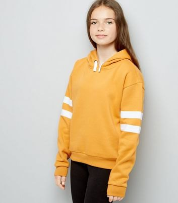 mustard hoodie with white striped sleeves