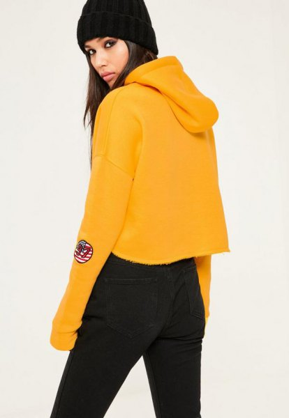 mustard yellow cropped hoodie with black high waisted jeans